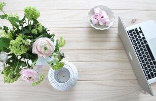 Laptop, weißes Windlicht und romantischer Blumenstrauß auf massiver Holztischplatte arrangiert