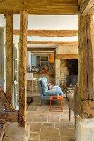 Blick in rustikalen Wohnbereich mit Natursteinboden und sichtbaren Balken