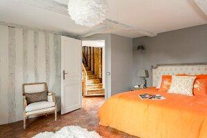 Doppelbett mit orangefarbener Bettwäsche in restauriertem Schlafzimmer mit Blick auf rustikale Holztreppe