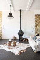 Cowhide rug on charcoal concrete floor and wood-burning stove in lounge area of loft apartment