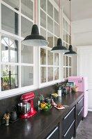 Black kitchen counter and pink fridge below interior windows in loft apartment