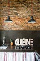 Black concrete kitchen worksurface and splashback on rustic brick wall