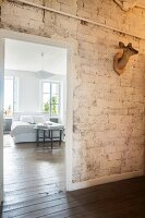 View from hallway with hunting trophy on unrendered brick wall into bright bedroom with wooden floor