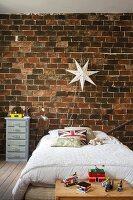 Bed below star-shaped lamp on rustic brick wall in boy's bedroom