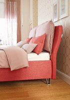 A salmon-coloured box spring bed with an upholstered frame and cushions