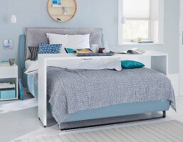A boxspring bed with a bed bridge in a bedroom in blue shades