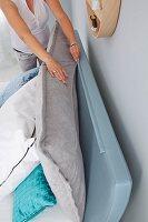 A woman zipping together a headboard cushion with a headboard