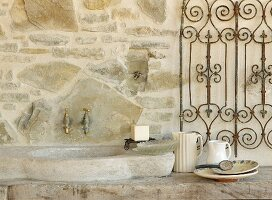 Stone sink and taps mounted on stone wall on terrace