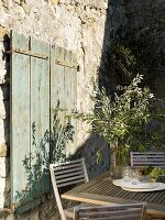 Olive branches in glass jar on wooden table next to rustic window shutters on Mediterranean terrace