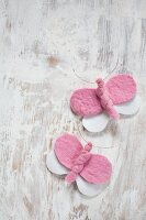 Pink and white, hand-made felt butterflies wrapped with copper wire on vintage wooden surface