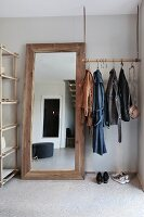 Minimalist coat rack suspended from ceiling on leather straps and hooks next to rustic full-length mirror
