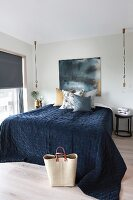 Double bed with dark blue bedspread flanked by minimalist pendant lamps