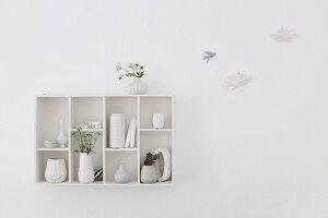 Wandboard mit Vasensammlung neben Vogelfiguren an der Wand