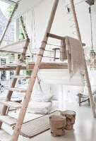 Free-standing gallery made from round timbers in loft-style interior