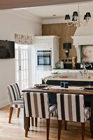 Island counter, set dining table and chairs with striped brown upholstery in white country-house kitchen