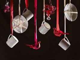 Cups, saucers and ornaments suspended from red ribbons