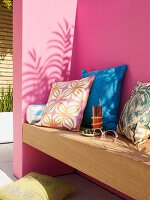 Scatter cushions with various patterns on wooden bench mounted on pink wall on terrace