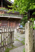 Vase of alliums on wooden table outside log cabin with balcony and open rustic garden gate