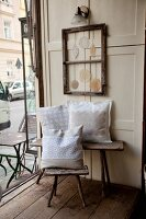 Rustic wooden furniture and lace cushions in vintage-style coffee house