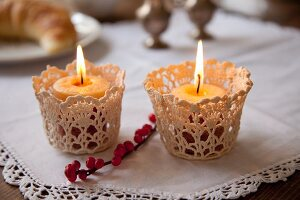 Romantic arrangement of two lit candles in crocheted holders on white tablecloth