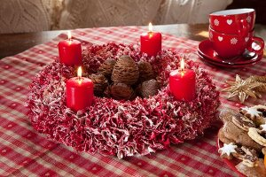 Hand-made, red and white fabric wreath with lit red candles and pine cones