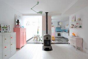 Log burner and pastel furniture in open-plan interior