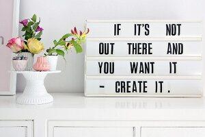 Retro-style motto in frame next to flower arrangement