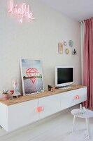 TV and picture on top of white floating sideboard below neon motto on patterned wallpaper