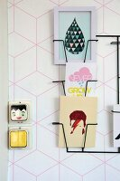 Delicate black magazine rack on wall with geometric, pink-patterned wallpaper