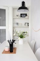Vase of ranunculus and beaker of black drinking straws on white dining table in front of open-fronted shelves of crockery