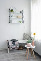 White wooden bench, laptop on blanket and classic String shelves in corner