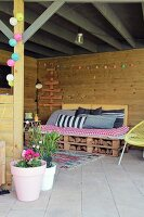 DIY pallet couch, cushions and colourful fairy lights on cosy, roofed terrace