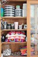 Colourful crocheted blanket, black and white crockery and candles in glass-fronted cabinet with sliding door