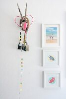 Pictures of animals in white frames and decorated hunting trophy on wall