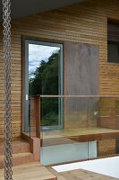 Detail of façade with wood cladding, glass door, metal panel, glass balustrade and steps