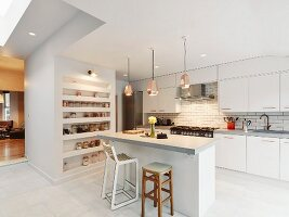 Free-standing counter below copper pendant lamps in open-plan modern kitchen with white cupboards