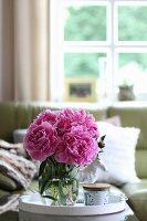 Pinkfarbene Pfingstrosen in Glasvase auf Sofatisch
