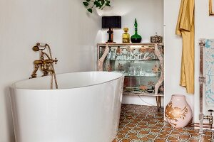 Modern, free-standing bathtub with vintage-style tap fittings in front of retro glass display case