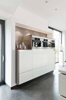A made-to-measure kitchen cupboard with built in devices in a framed alcove