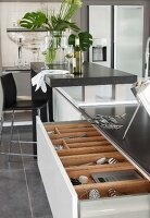 A kitchen island with a half-opened drawer and a view of a cutlery divider