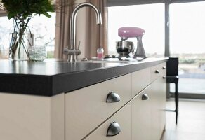 A kitchen island with a white cupboard, shell handles and a built-in sink