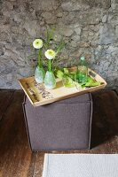 Wooden tray and-decorated with floral pattern on top of square pouffe against stone wall