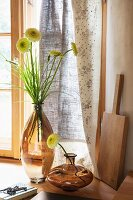 Arrangement of glass vases and flowers in front of printed curtain