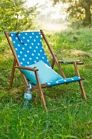 A deckchair with homemade fabric cover on green grass in a garden