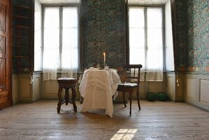 Round table, stool and vintage wooden chair in front of blue patterned wallpaper and windows in 19th-century Italian villa