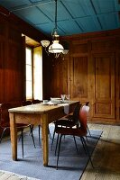 Rustic wooden dining table and chairs next to window in wood-clad dining room
