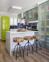 Translucent cupboards and breakfast bar in modern kitchen
