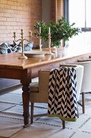 Rustic wooden table and upholstered chairs in front of brick wall