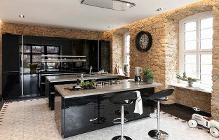 A modern kitchen with shiny, black wooden surfaces and two islands in a rustic period building with sandstone walls