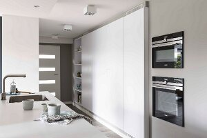Detail of a kitchen counter opposite a modern, built-in kitchen cupboard in white in an open-plan kitchen